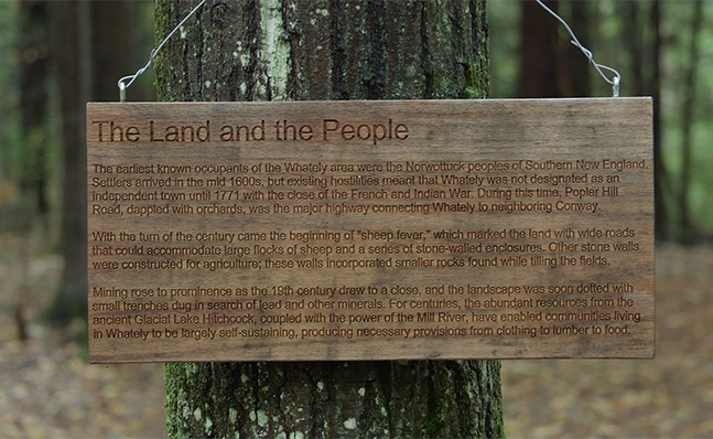 "A close-up of a wooden sign posted in Whately, ""The Land and the People"""