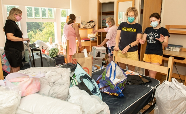 family helping a student set up her room