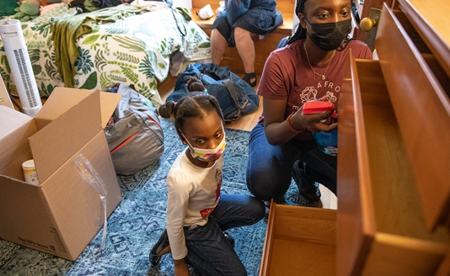 a student and child setting up a new room's dresser