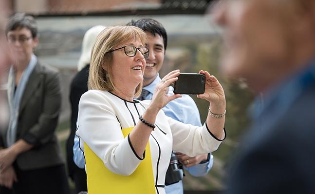 President Kathy McCartney takes a photo at the Neilson groundbreaking