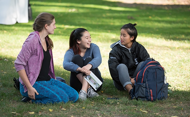 Three students on the lawn at the Neilson groundbreaking