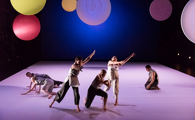 Four dances onstage with a backdrop of colored circles