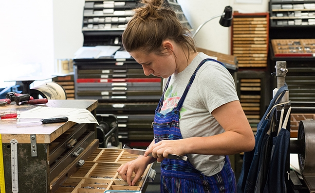 Student working in the type shop