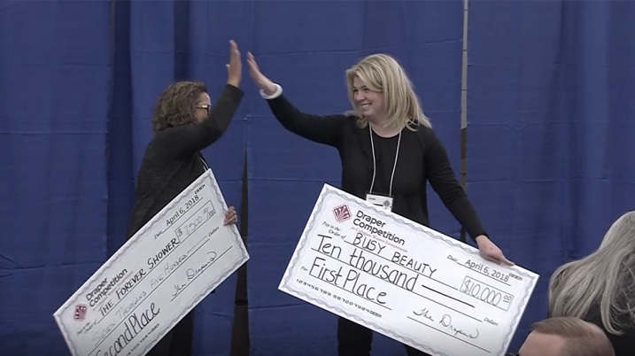 Two winners at the 2018 Draper Competition holding checks