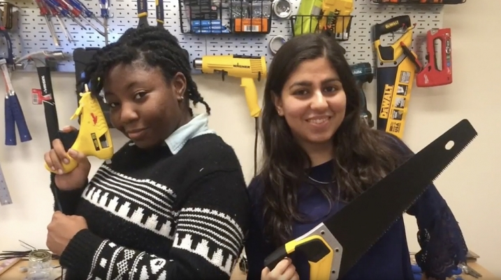 Video still of two students holding tools