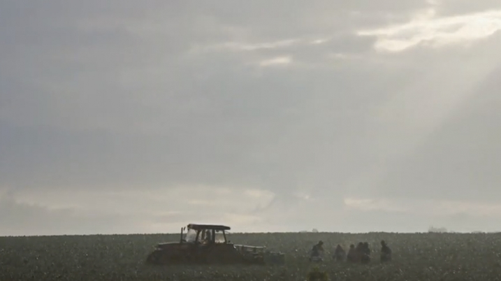 Video still of a field and tractor