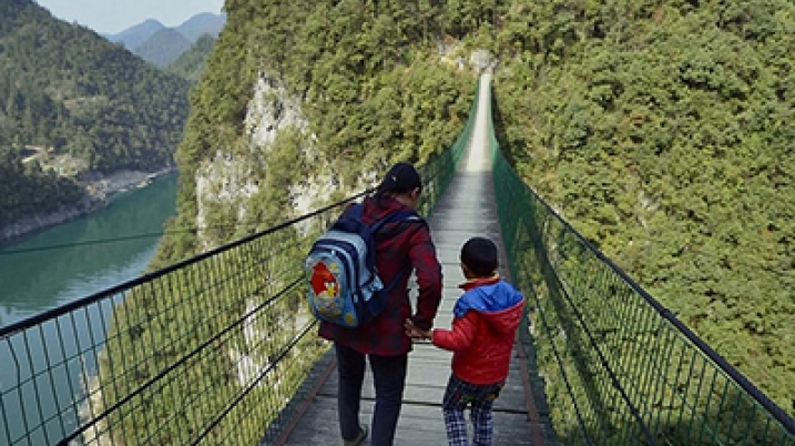 Woman takes the hand of a small boy and cross a tall bridge
