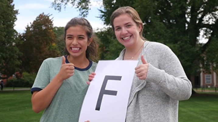 "Smith students give thumbs up holding a piece of paper with big ""F"""