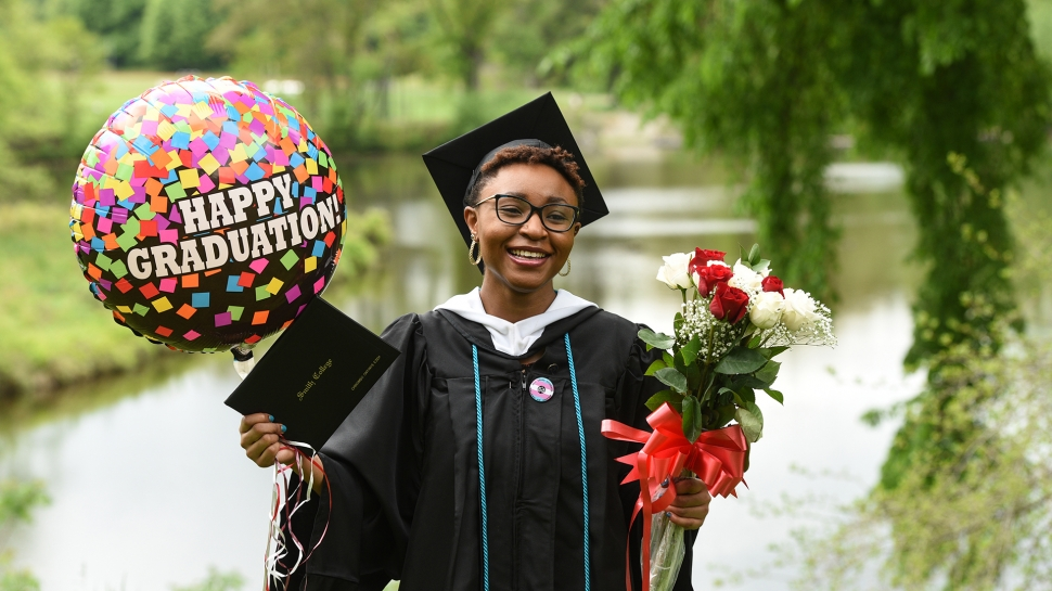 Student in cap and gown, with balloon and flowers