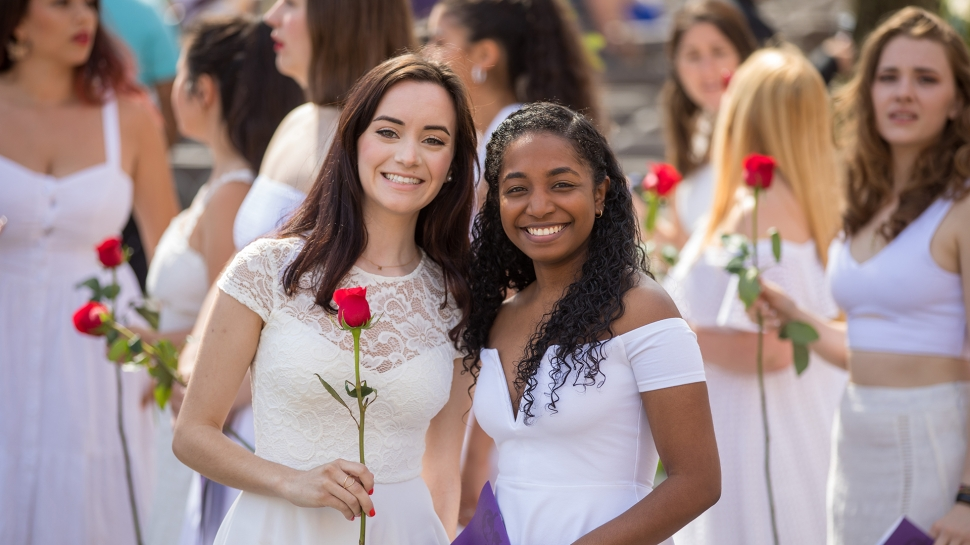 Two students in white Ivy Day dresses holding red roses