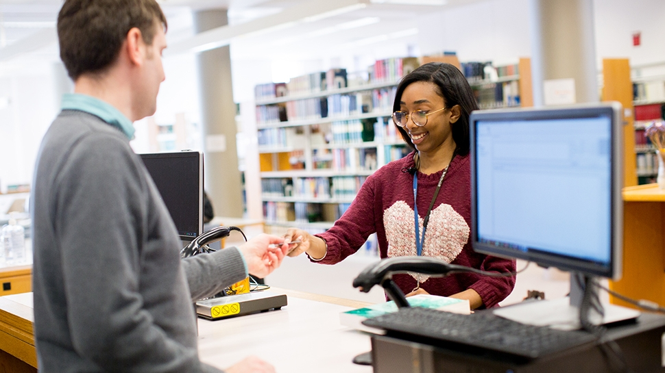 Student at the reference desk at Young Library